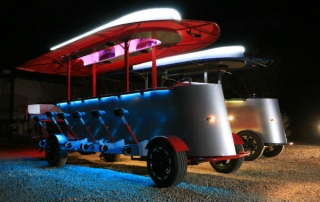 Two Pedal Crawler bar bikes lit up at night with party lights